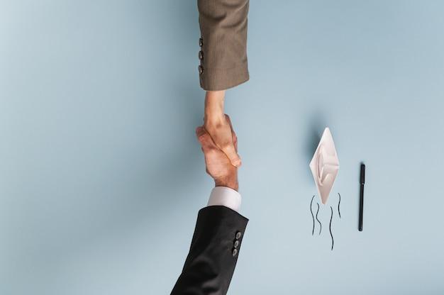Vista superior do empresário e empresária apertando as mãos em acordo e colaboração