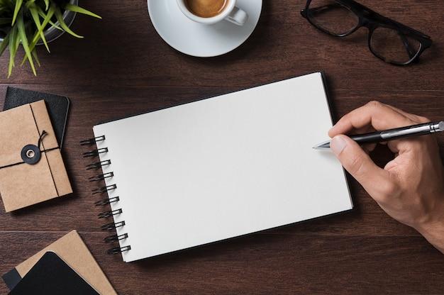 Vista superior do empresário escrevendo no caderno.