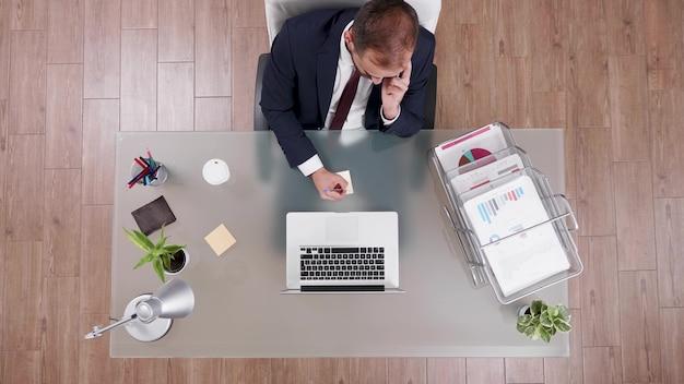 Vista superior do empresário falando ao telefone com o parceiro escrevendo lucro corporativo no stickey notes