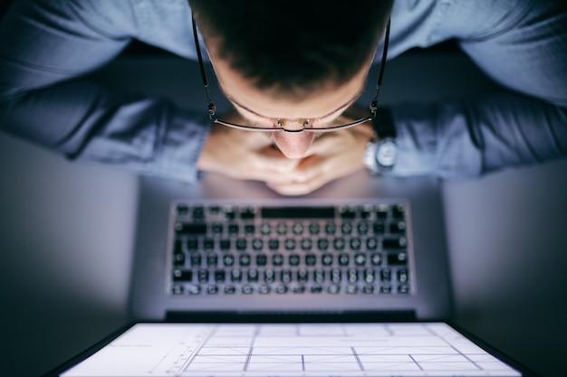 Vista superior do empresário, olhando para o laptop enquanto está sentado no escritório, tarde da noite.