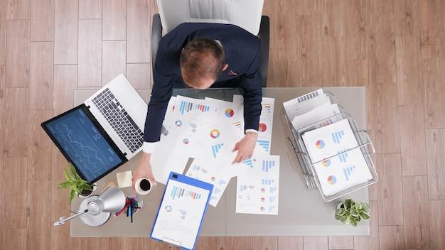 Vista superior do empresário segurando uma xícara de café enquanto digita as estatísticas da empresa