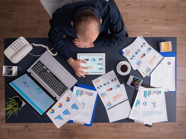 Vista superior do empresário usando o tablet pc, analisando documentos e gráficos financeiros, sentado à mesa no escritório corporativo