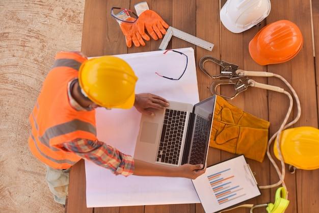 Vista superior do engenheiro arquitetônico, usando o laptop em suas plantas com documentos no canteiro de obras.