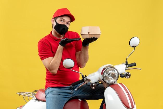 Vista superior do entregador confiante e satisfeito usando blusa vermelha e luvas de chapéu na máscara médica, sentado na scooter, mostrando o pedido