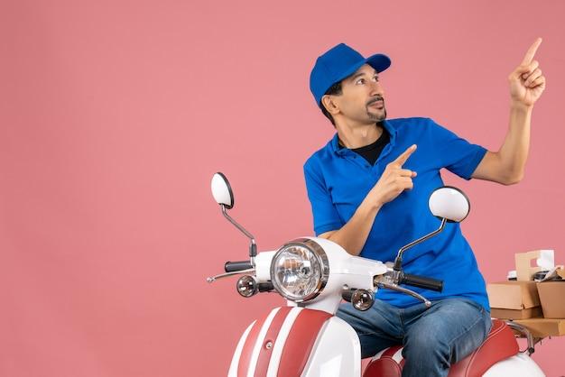 Vista superior do entregador de chapéu sentado na scooter, entregando pedidos, voltado para cima, apontando para cima no fundo cor de pêssego