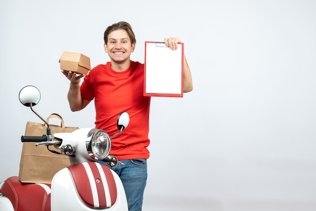 Vista superior do entregador feliz, de uniforme vermelho, em pé perto da scooter, segurando o pedido e o documento no fundo branco