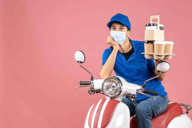 Vista superior do entregador masculino concentrado com máscara e chapéu, sentado na scooter, entregando pedidos em fundo cor de pêssego