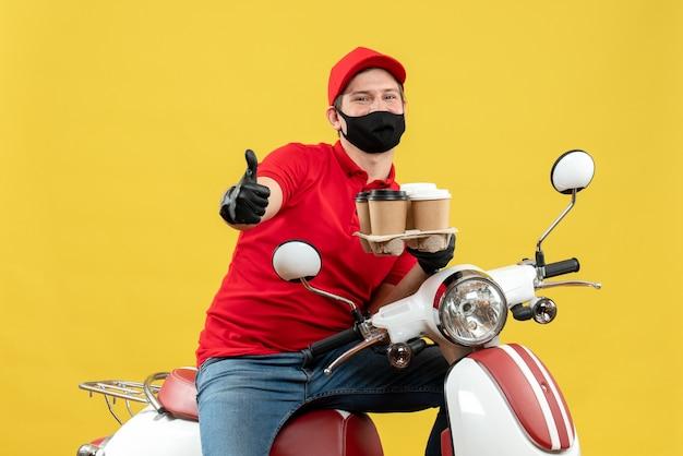 Vista superior do entregador sorridente, usando uniforme e luvas de chapéu, máscara médica, sentado na scooter, mostrando ordens e fazendo gesto de ok