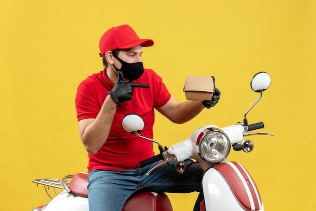 Vista superior do entregador usando blusa vermelha e luvas de chapéu na máscara médica, sentado na scooter, apontando a ordem