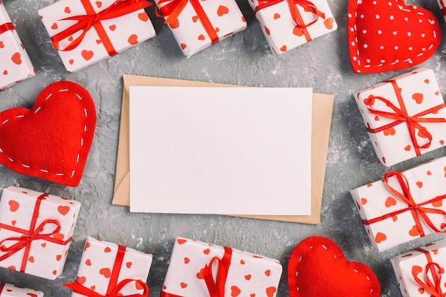 Vista superior do envelope do ofício, cartão em branco, corações vermelhos têxtil e caixas de presente