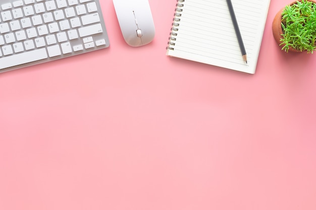 Vista superior do escritório de mesa em rosa pastel com espaço de cópia para inserir o texto.