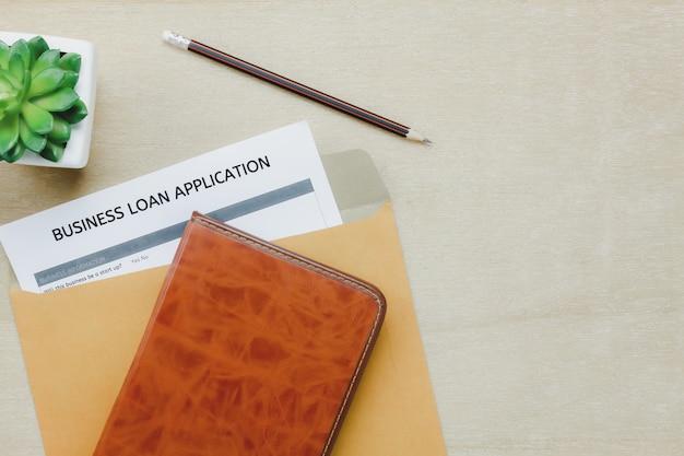 Vista superior do escritório do escritório de negócios. o appcation do empréstimo do negócio forma a carta do lápis e a árvore do diário no fundo da tabela de madeira com espaço da cópia.
