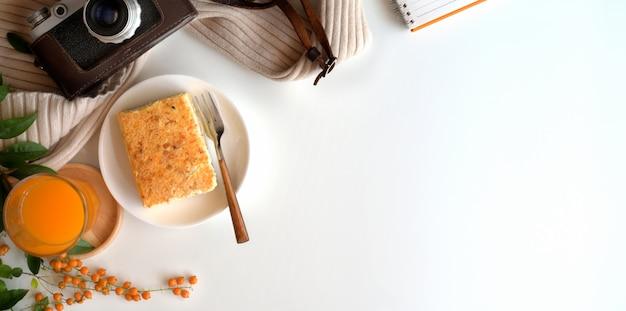 Vista superior do espaço de trabalho acolhedor com um copo de suco de laranja e torradas de pão