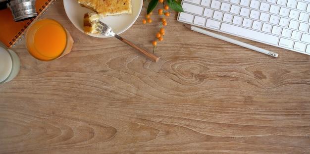 Vista superior do espaço de trabalho aconchegante com um copo de suco de laranja e torradas de pão na mesa de madeira