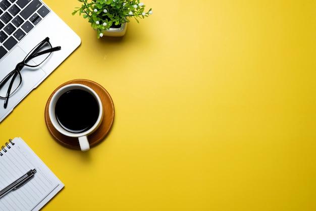 Vista superior do espaço de trabalho amarelo com teclado de café, óculos, espaço de cópia.