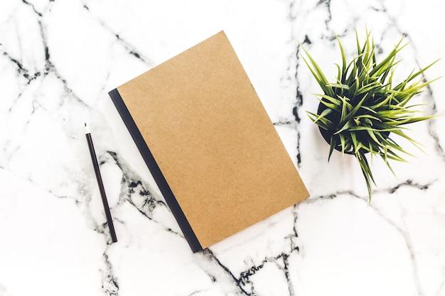 Vista superior do espaço de trabalho com caderno e lápis no fundo de mármore branco.