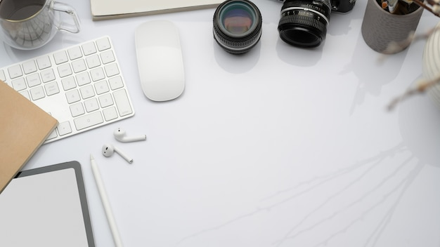 Vista superior do espaço de trabalho com dispositivos digitais, câmera e suprimentos de escritório, lay-out plana