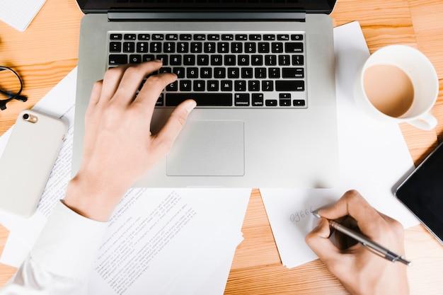 Vista superior do espaço de trabalho com laptop e café