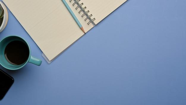 Vista superior do espaço de trabalho com o caderno em branco aberto, a xícara de café e o ritmo de cópia na sala de home office