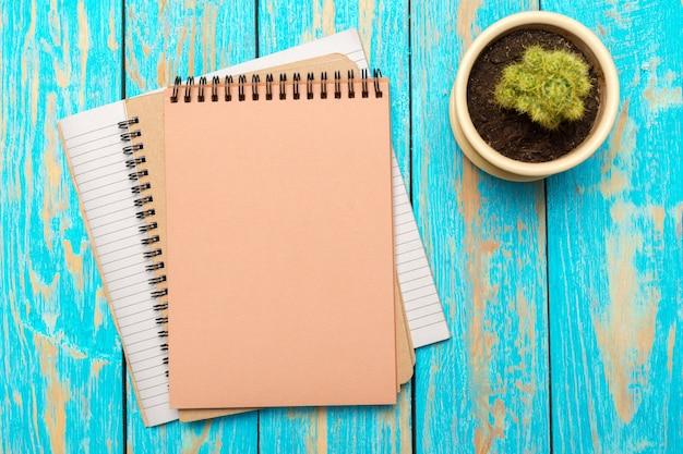Vista superior do espaço de trabalho com o caderno em branco e caneta na mesa de madeira