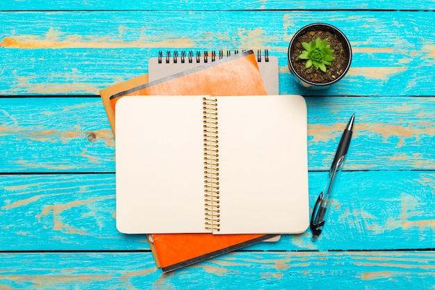 Vista superior do espaço de trabalho com o caderno em branco e caneta no fundo da mesa de madeira