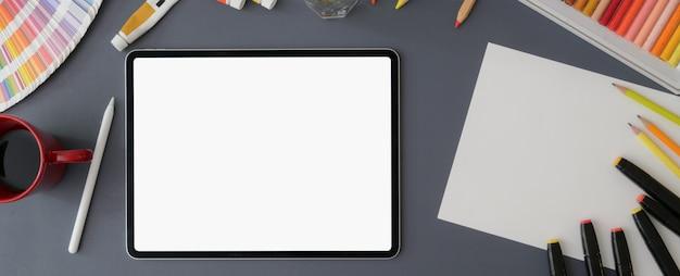 Vista superior do espaço de trabalho com tablet de tela em branco, esboço de papel, ferramentas de pintura e xícara de café