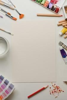 Vista superior do espaço de trabalho criativo de um artista plano com simulação de papel e ferramentas de pintura na sala de escritório em casa
