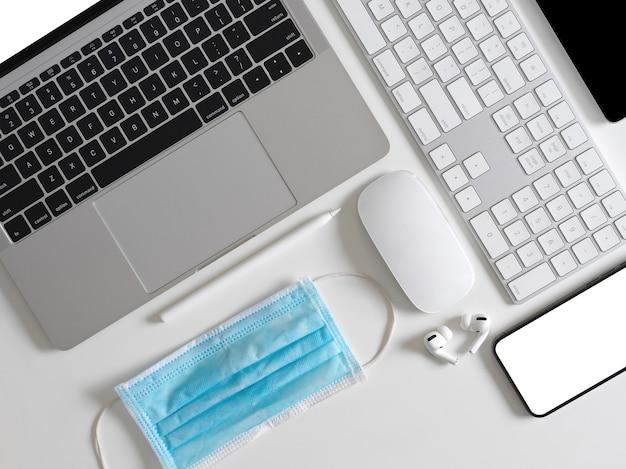 Vista superior do espaço de trabalho criativo plano com laptop, smartphone, teclado de computador, máscara cirúrgica e acessórios
