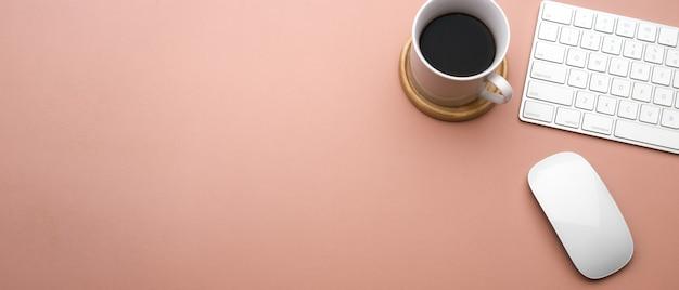 Vista superior do espaço de trabalho criativo rosa plano com xícara de café, teclado, mouse e espaço de cópia