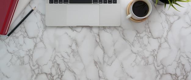 Vista superior do espaço de trabalho da moda com laptop, artigos de papelaria, xícara de café