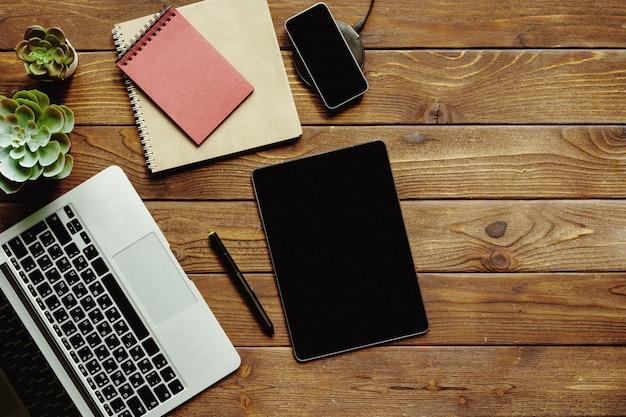 Vista superior do espaço de trabalho da tabela do office. mesa de madeira com laptop, dispositivos e planta