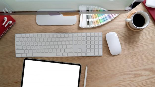 Vista superior do espaço de trabalho de design com tablet, computador e material de escritório na mesa rústica moderna