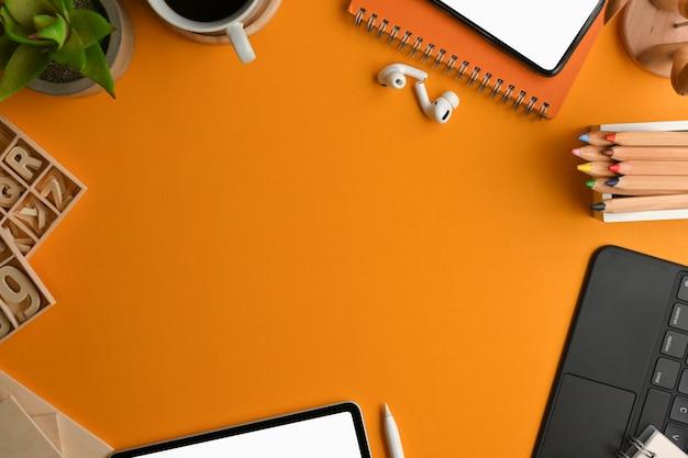 Vista superior do espaço de trabalho do artista com artigos de papelaria, elemento de artesanato, dispositivo digital e espaço de cópia na mesa amarela