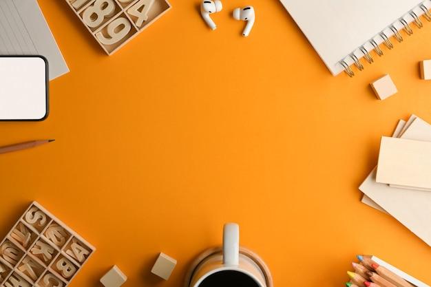 Vista superior do espaço de trabalho do artista com artigos de papelaria, elemento de artesanato, xícara de café e espaço de cópia na mesa amarela