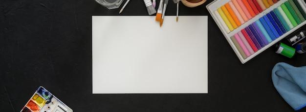 Vista superior do espaço de trabalho do artista com papel de desenho, pastéis de óleo e ferramentas de pintura