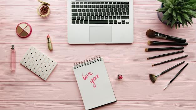 Vista superior do espaço de trabalho do blogueiro de moda com cosméticos de laptop e mulher, ferramentas de maquiagem e acessório na superfície de cor. conceito de beleza e moda.