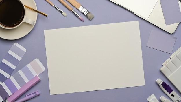Vista superior do espaço de trabalho do designer com simulação de papel, ferramentas de pintura e xícara de café na mesa roxa