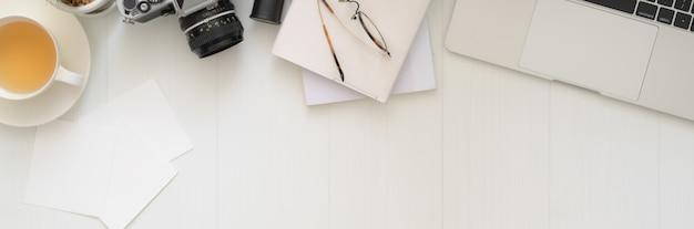 Vista superior do espaço de trabalho do fotógrafo com laptop, câmera, suprimentos, xícara de chá e espaço de cópia