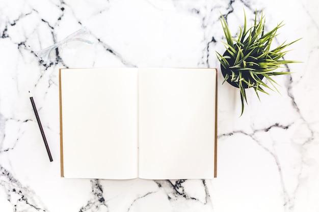 Vista superior do espaço de trabalho e caderno aberto com páginas em branco de simulação