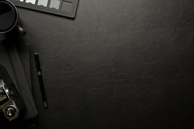 Vista superior do espaço de trabalho escuro e plano criativo com suprimentos de papelaria para câmera e espaço de cópia na mesa preta
