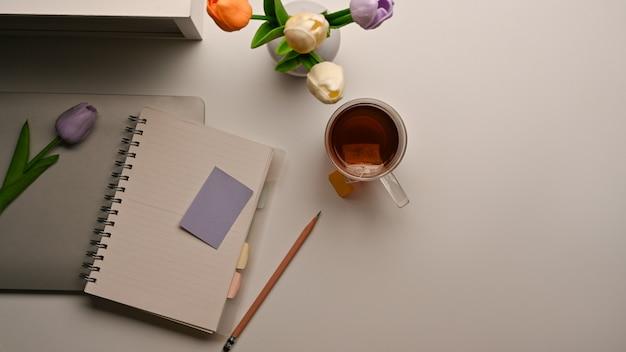 Vista superior do espaço de trabalho feminino com notebook, laptop, xícara de café, vaso de flores