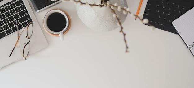 Vista superior do espaço de trabalho moderno com computador portátil, material de escritório e xícara de café na mesa branca