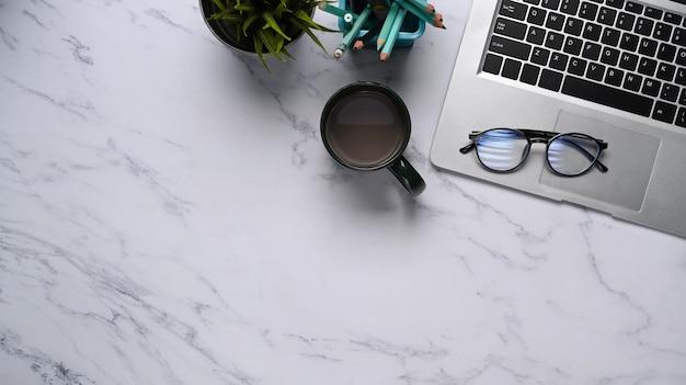 Vista superior do espaço de trabalho moderno com laptop, xícara de café, artigos de papelaria, copos e espaço de cópia na mesa de mármore.