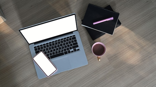 Vista superior do espaço de trabalho simples com laptop de tela em branco, telefone celular, xícara de café e caderno na mesa de madeira.
