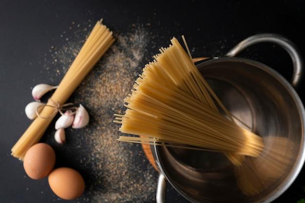 Vista superior do espaguete duro cru em uma panela de metal, água fervente, ingredientes para cozinhar arounds