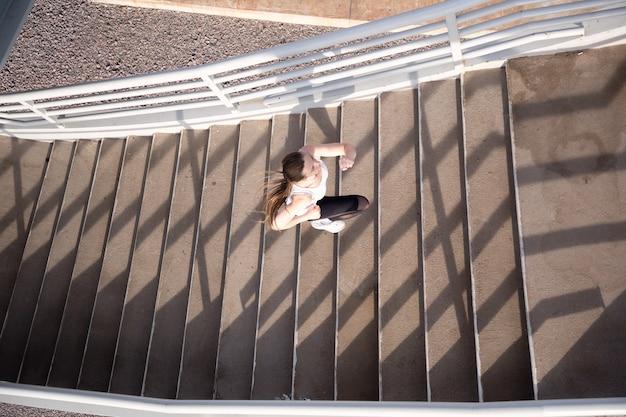 Vista superior do esportista subindo as escadas para a ponte