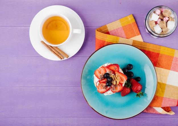 Vista superior do estaladiço saboroso com morangos maduros de mirtilos e nozes com creme de leite em um prato de cerâmico, servido com uma xícara de chá verde sobre fundo roxo de madeira