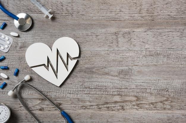 Vista superior do estetoscópio com coração tendo sinal de cardio e medicamento na mesa do médico.