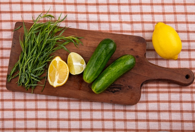 Vista superior do estragão em uma placa de madeira da cozinha com fatias de limão de pepino em uma superfície de toalha de mesa marcada