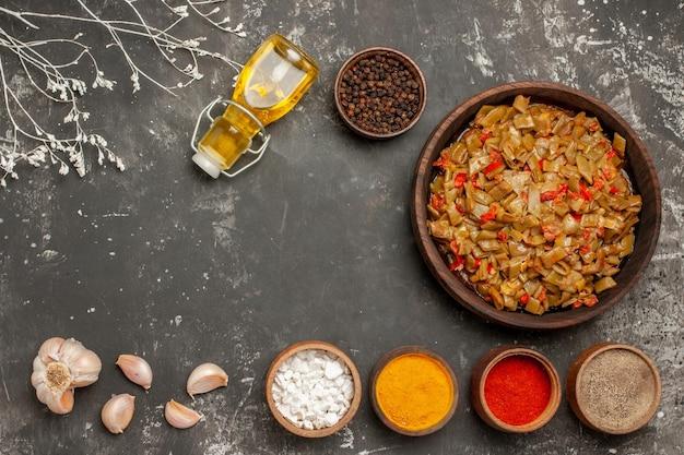 Vista superior do feijão verde feijão verde no prato ao lado da garrafa de alho de especiarias coloridas de óleo na mesa escura